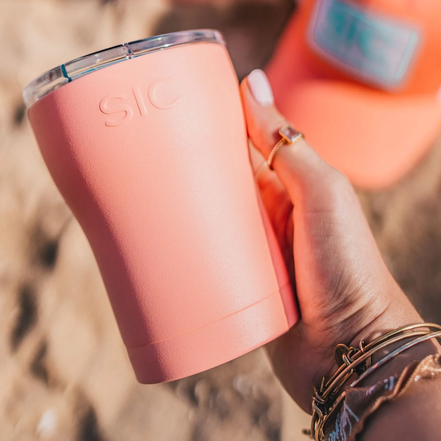 woman holds a SIC 12 oz. cup