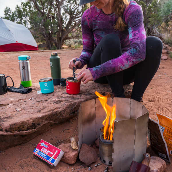 woman using Solo camp stove wind protection screen camping