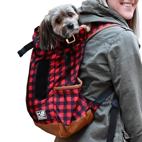 A small dog being carried in a red plaid K9 Sport Sack